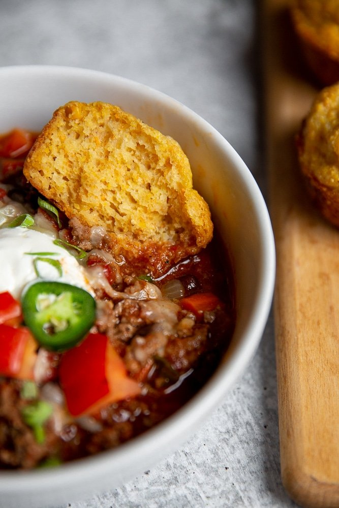 Close-up of a cornbread muffin dunking into a bowl of chili.