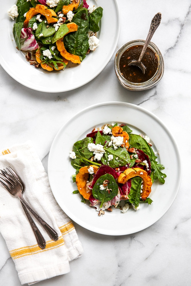 Overhead shot of the roasted squash salad on a table with a jar of dressing to the side.