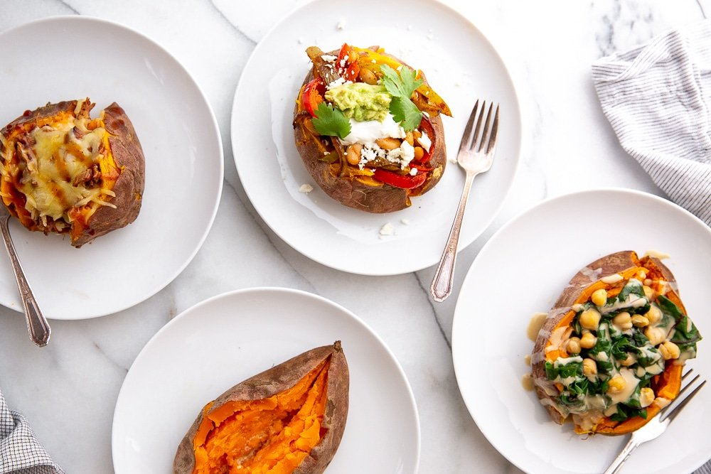 Overhead shot of slow cooker sweet potatoes loaded with different toppings.