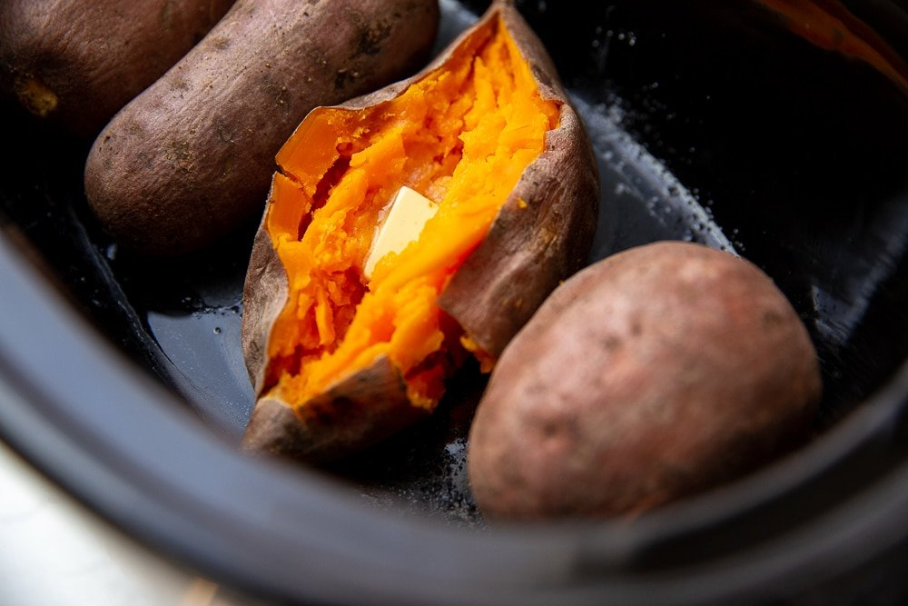Close up of a buttered sweet potato in a slow cooker.