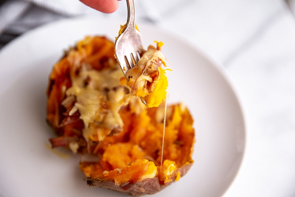 Close up of a loaded sweet potato stuffed with barbecue pork and cheddar cheese.