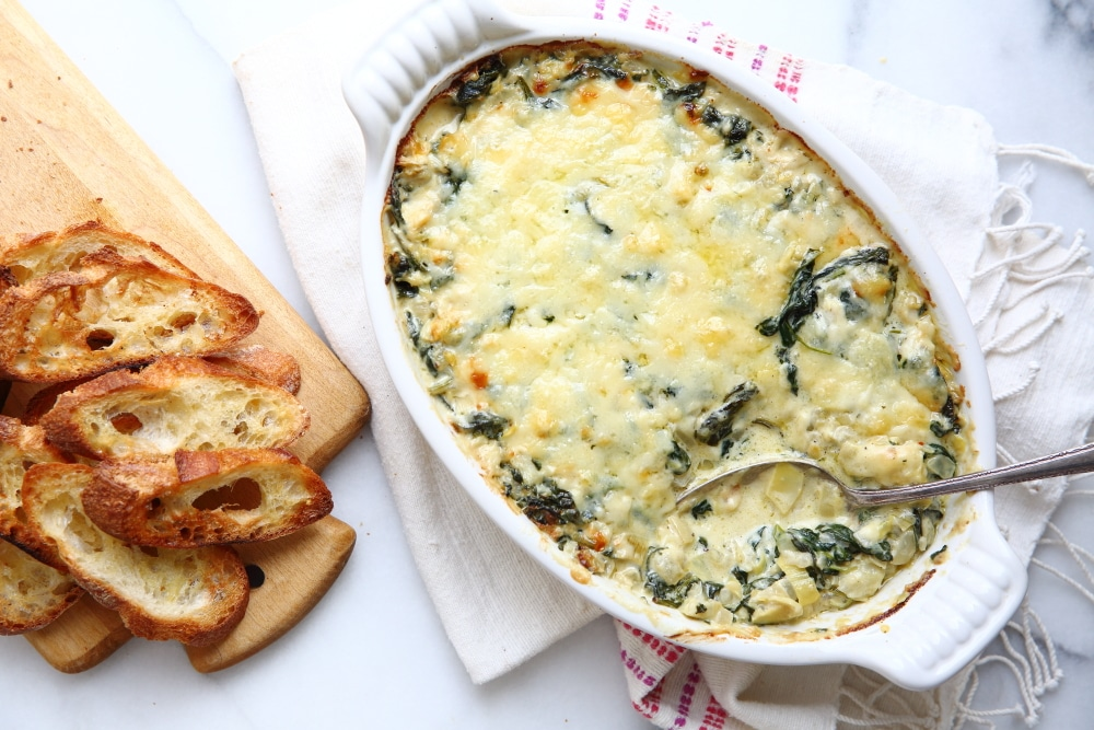 Overhead shot of spinach and artichoke dip in a baking dish with toasted bread alongside.