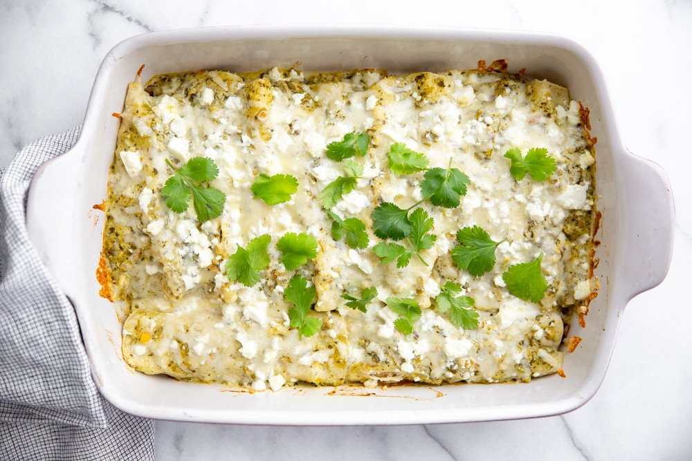 Green salsa enchiladas in a baking dish, sprinkled with cilantro.