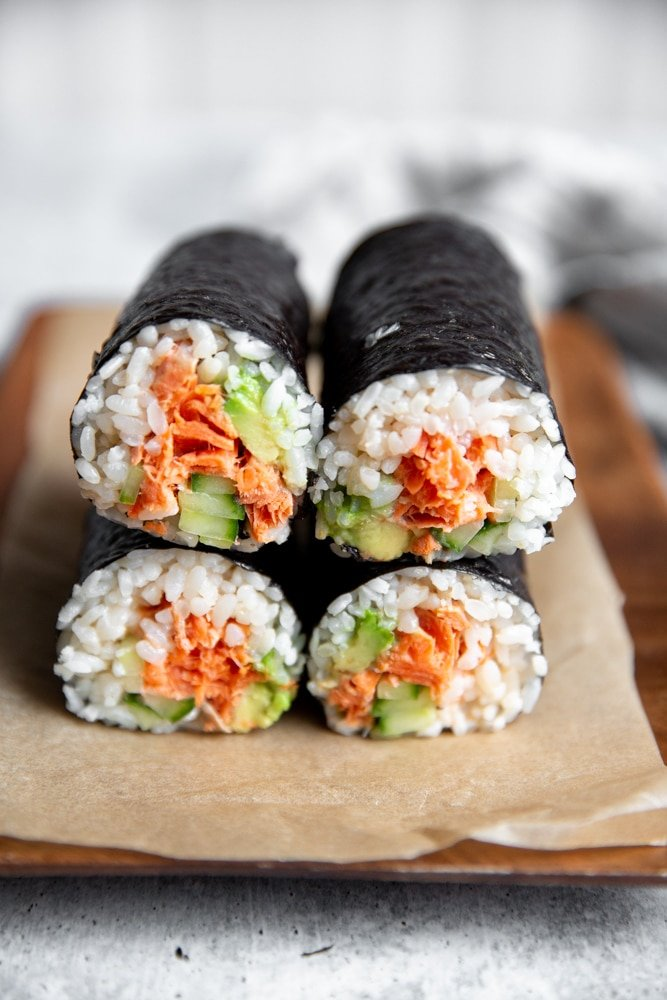 Spicy salmon sushi burrito rolls stacked on top of each other on a serving board.