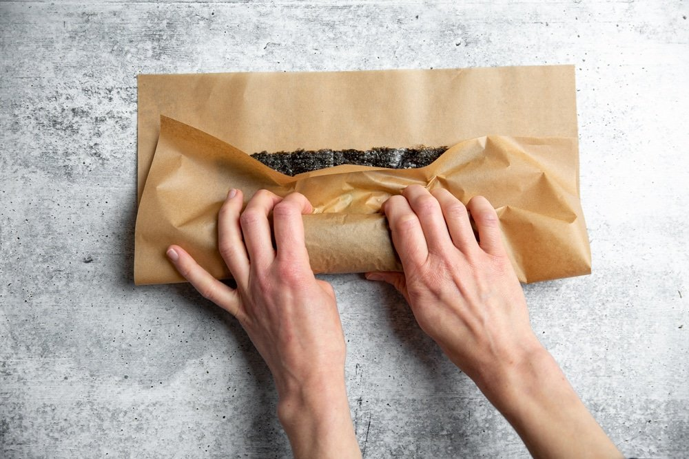 Hands using a piece of parchment paper to roll a salmon sushi roll.