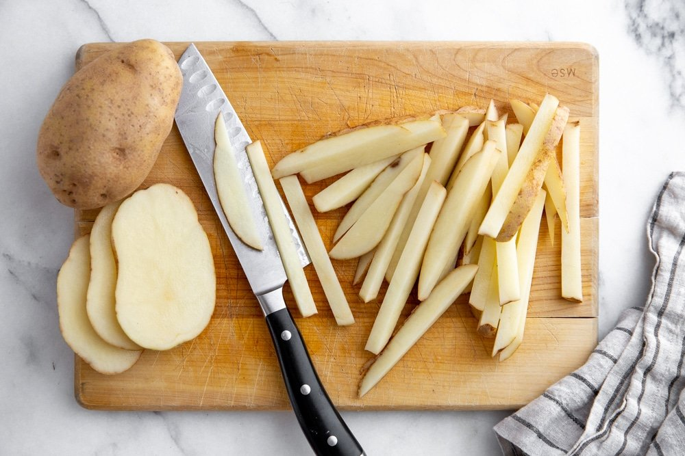 Process shot showing how to cut potatoes into french fries.