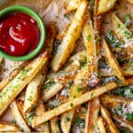 Baked french fries with herbs and parmesan on parchment paper with ketchup.