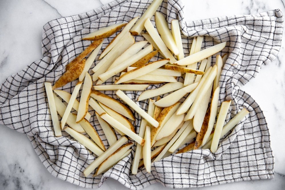 Process shot showing soaked French fries drying in a kitchen towel before baking.