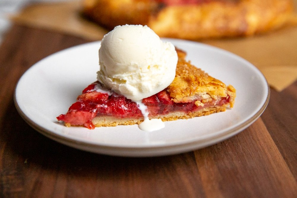 A slice of strawberry galette topped with a scoop of vanilla ice cream.