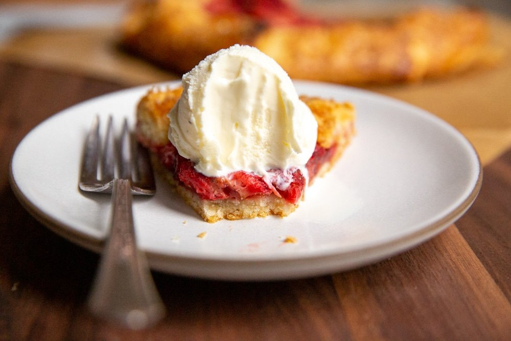 Slice of strawberry galette with ice cream on a plate with bite taken out.