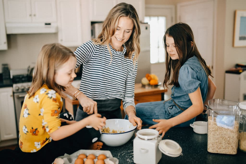 Nicki Sizemore cooking with her daughters in her kitchen.