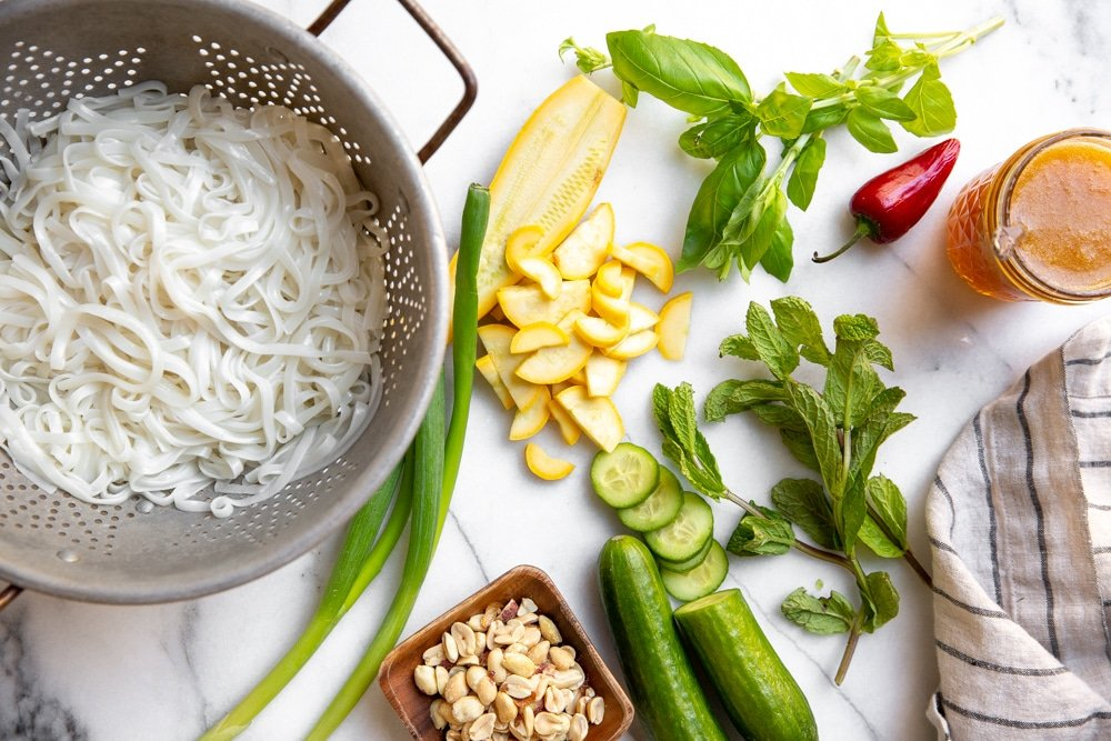 The ingredients for the rice noodle salad arranged on a marble countertop.