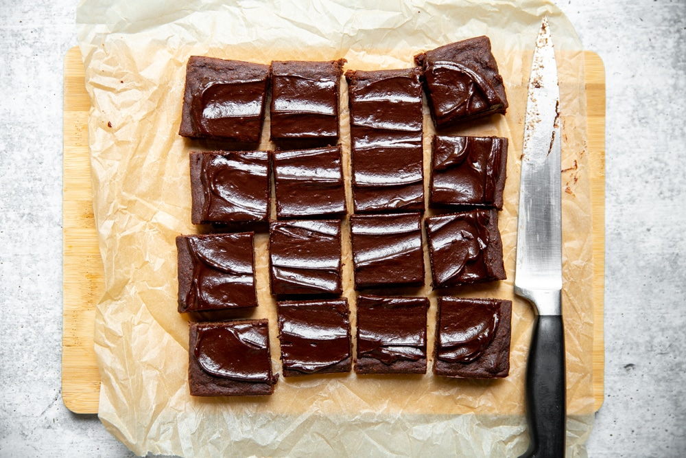 Overhead shot of brownies on a cutting board with a knife.