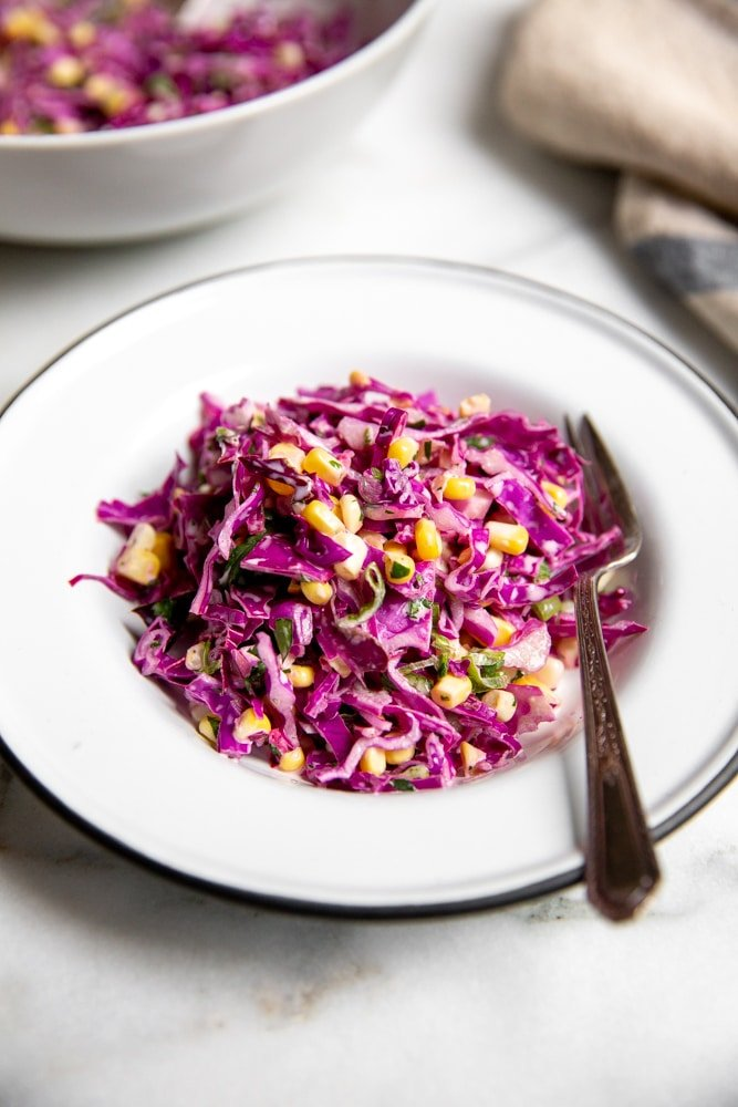 Close up of red cabbage coleslaw in a bowl with a fork.