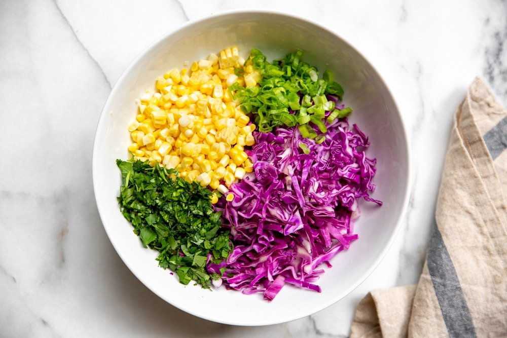 All of the ingredients for the red cabbage slaw arranged in a large bowl.