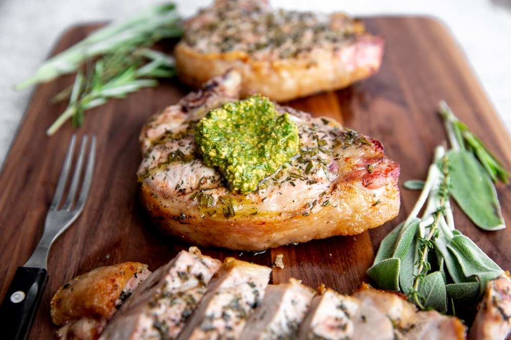 Close up of a grilled pork chop on a serving board.