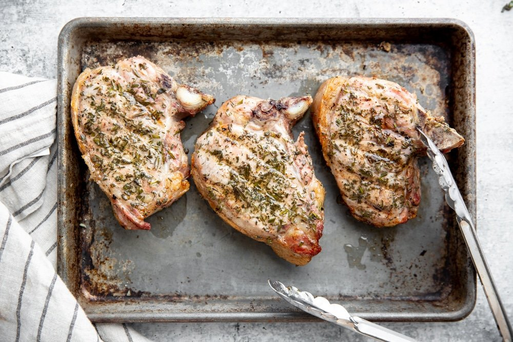 Grilled thick cut pork chops on a sheet tray with tongs.