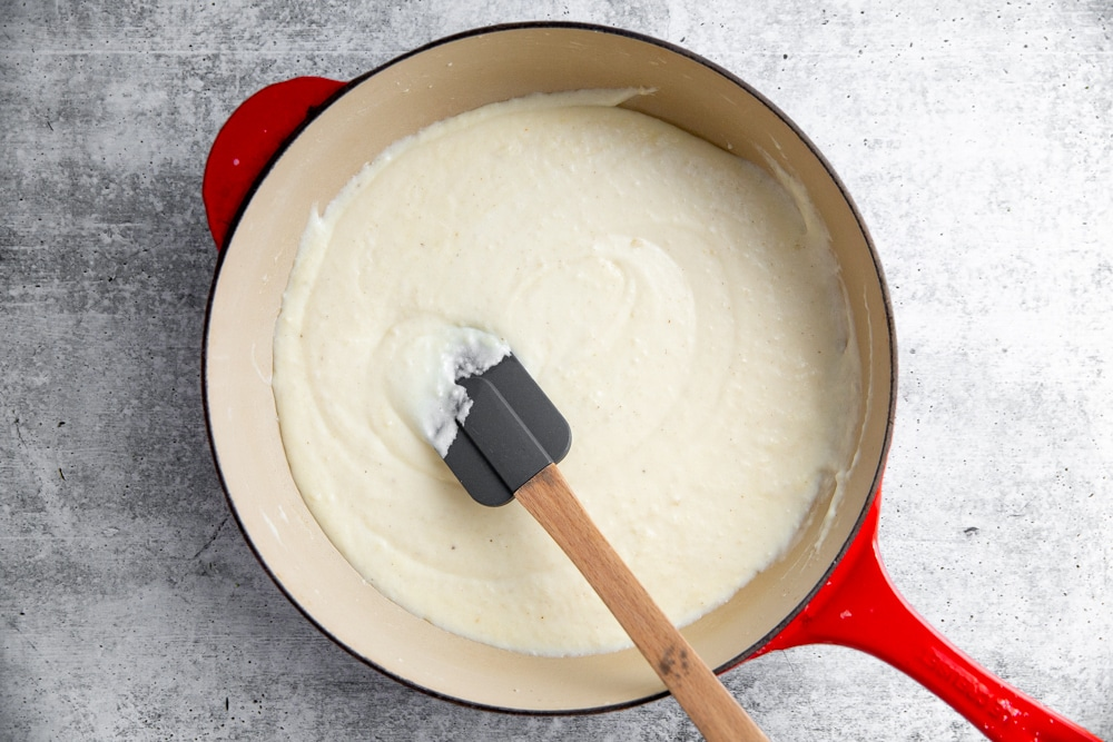 Creamy white sauce in a large skillet with a spatula.