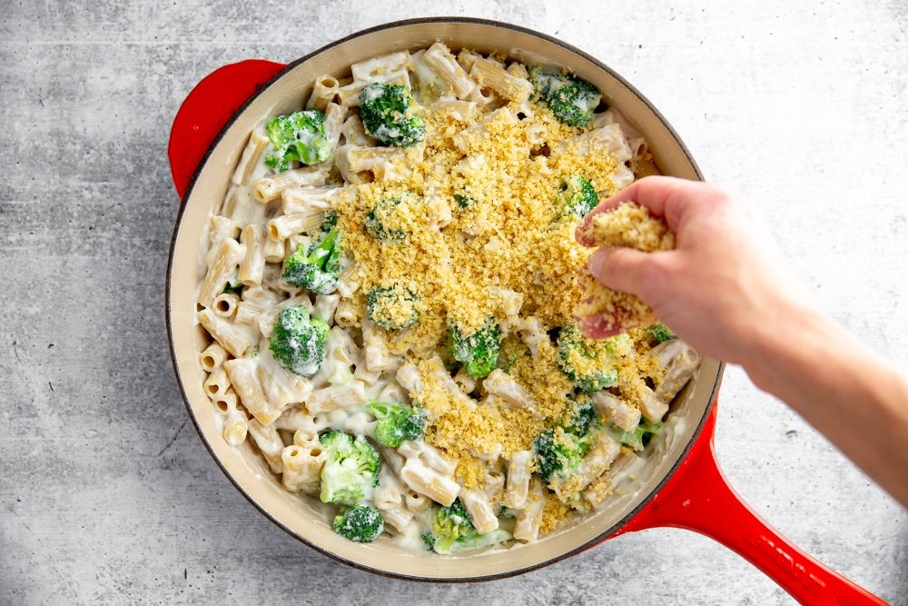 Hand sprinkling the breadcrumb topping over the broccoli pasta bake.