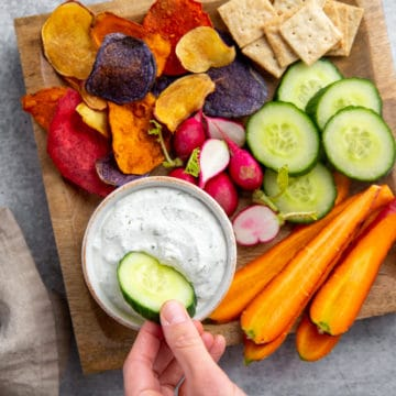 Hand dipping a cucumber into the healthy cottage cheese veggie dip, with other veggies alongside.
