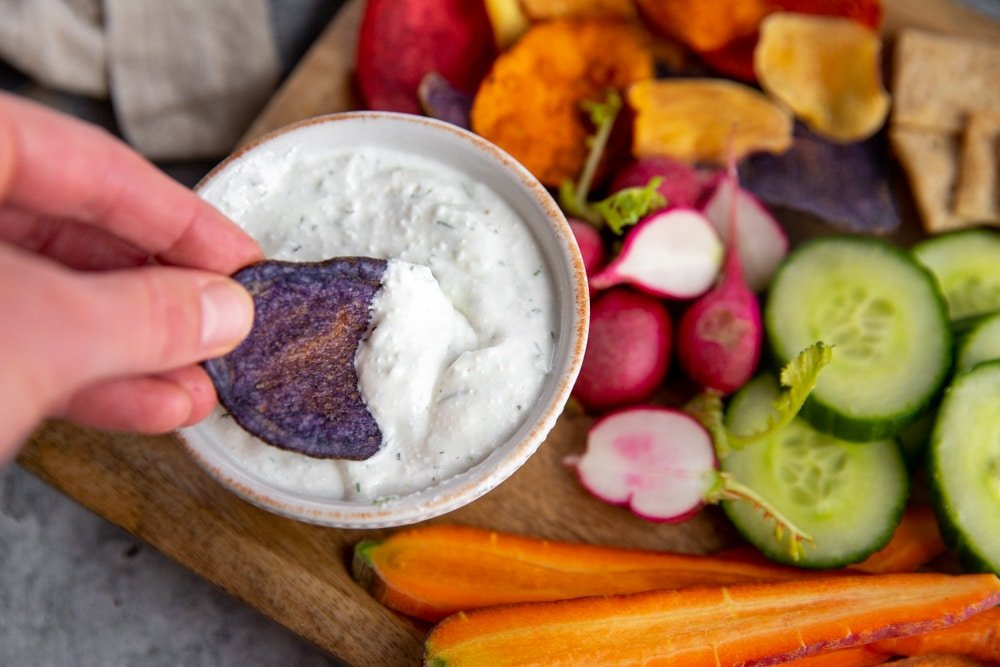 Hand dipping a purple potato chip into the healthy veggie dip.