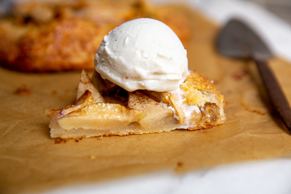 A slice of apple galette on a piece of parchment paper, topped with a scoop of vanilla ice cream.