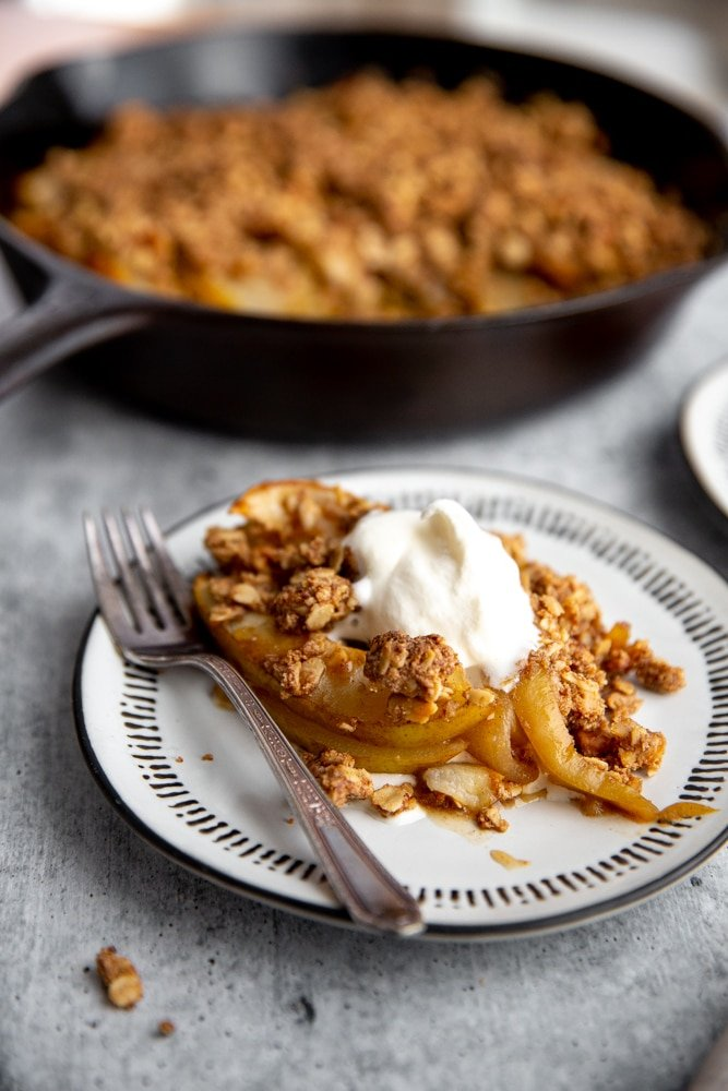 A serving of pear crisp on a plate, topped with whipped cream.