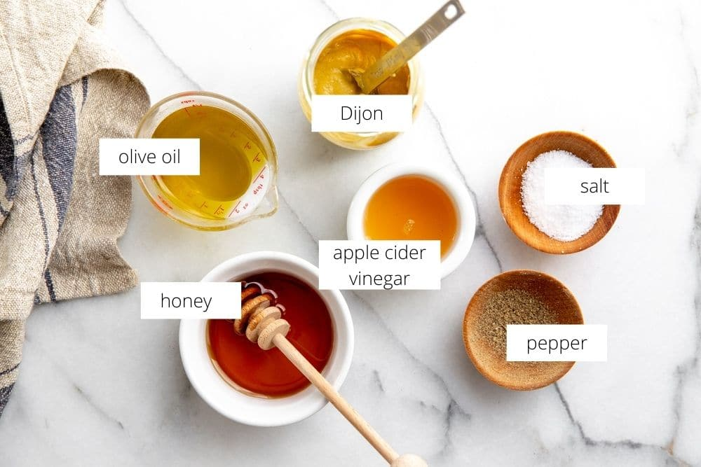 All of the apple cider vinaigrette ingredients arranged on a marble surface.