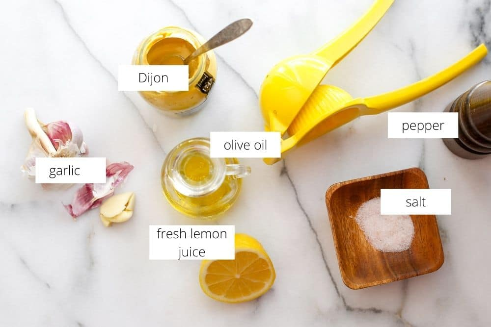 Salad dressing ingredients on a marble surface.