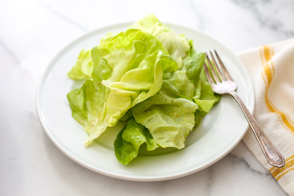 Close up of a green salad on a plate with a fork.