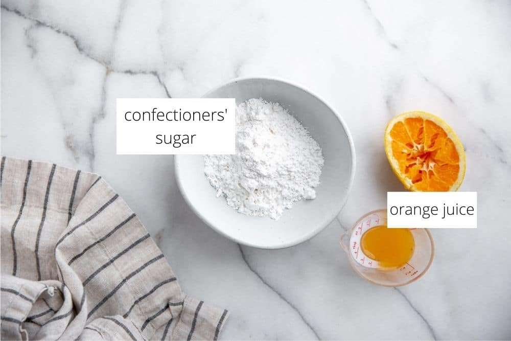 The ingredients for the orange glaze on a marble surface.