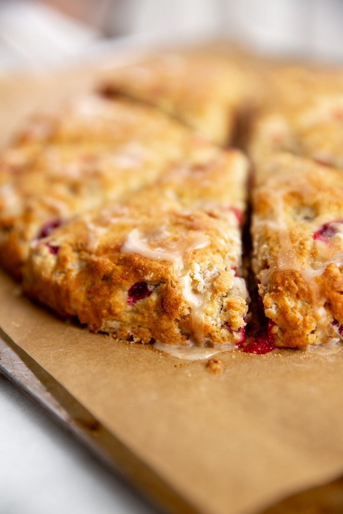 Close up of the a cranberry scone with orange glaze on a parchment lined baking sheet.