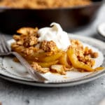 Gluten free pear crumble on a plate topped with whipped cream.