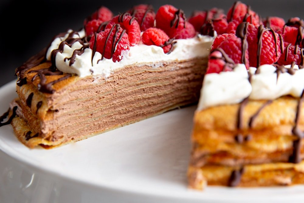 Crepe cake on a platter with a slice removed.