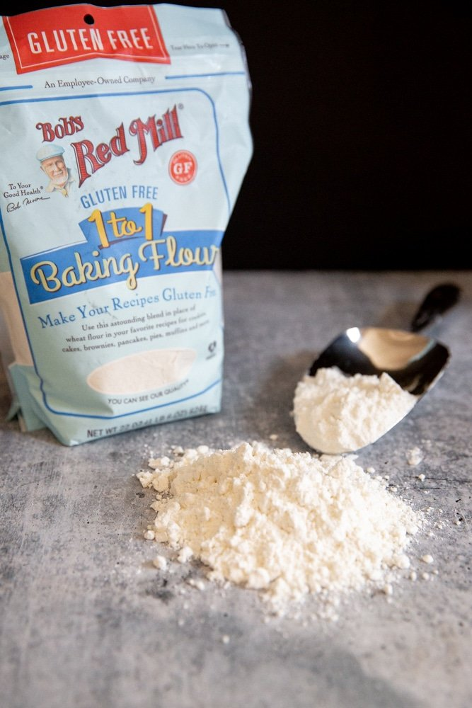 A bag of gluten free flour with a pile of flour in the foreground.