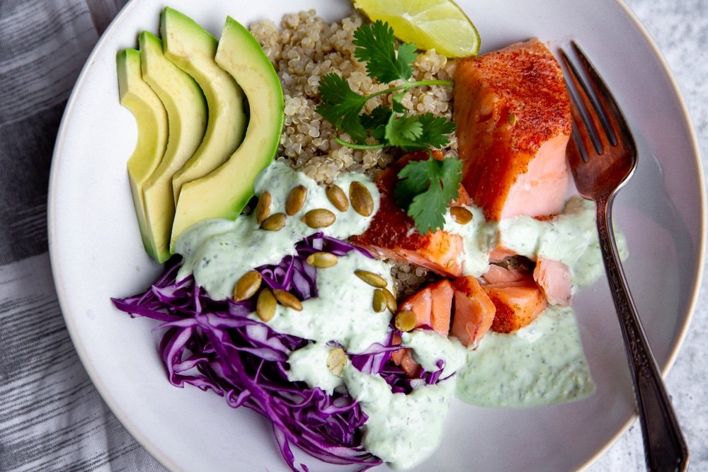 Close up of the cilantro yogurt sauce drizzled over a power bowl featuring salmon, avocado and shaved red cabbage.