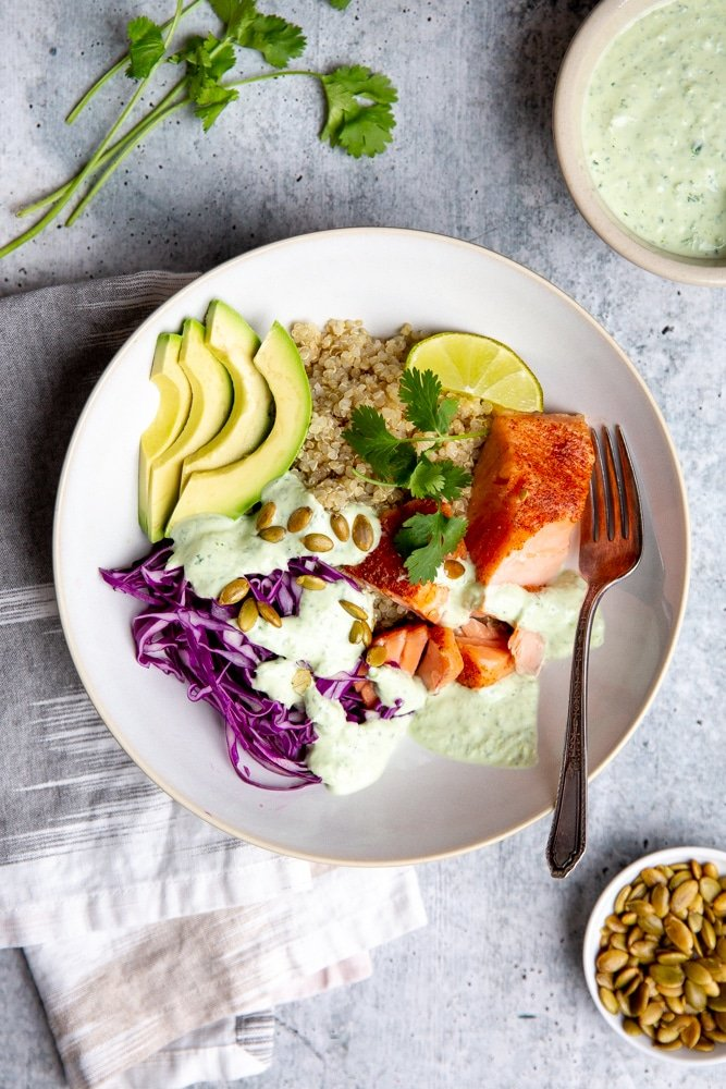 Grain bowl with salmon, cabbage and avocado, drizzled with cilantro yogurt sauce.