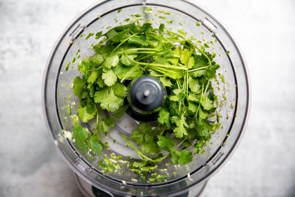 Process shot showing the cilantro in the food processor for the cilantro yogurt sauce.