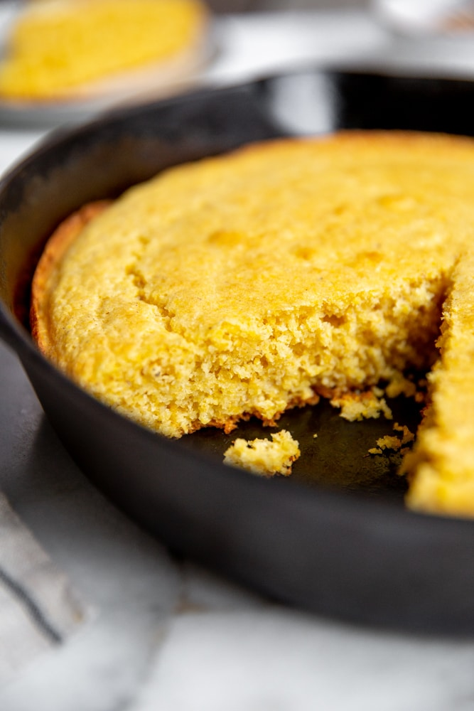 Close up of a cut piece of cornbread in a skillet.