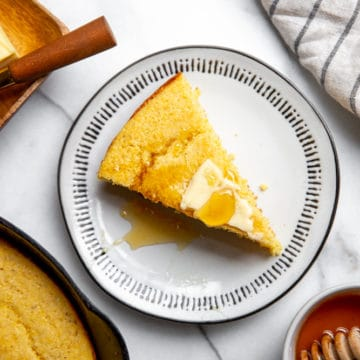 A slice of gluten free cornbread on a plate topped with butter and honey.