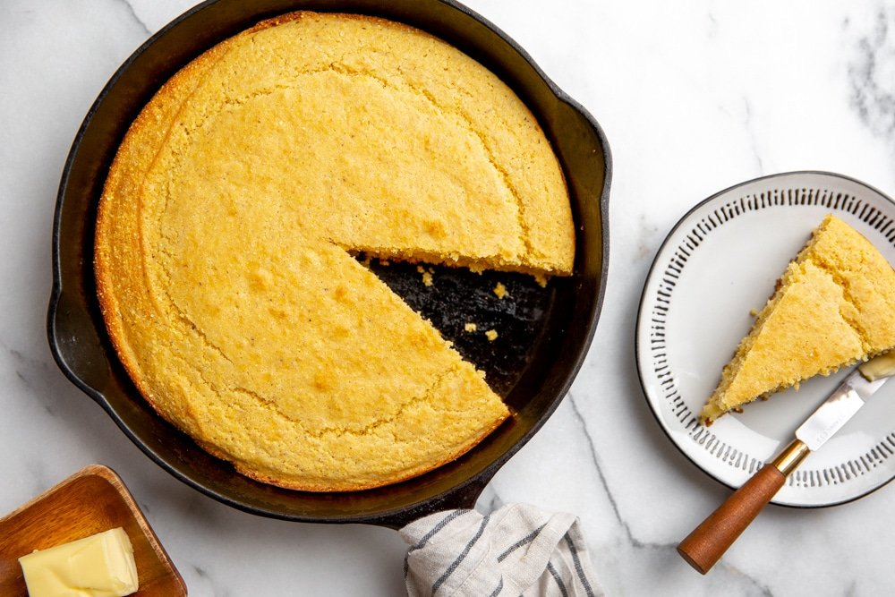 Skillet cornbread on a marble surface with a wedge removed and on a plate alongside.