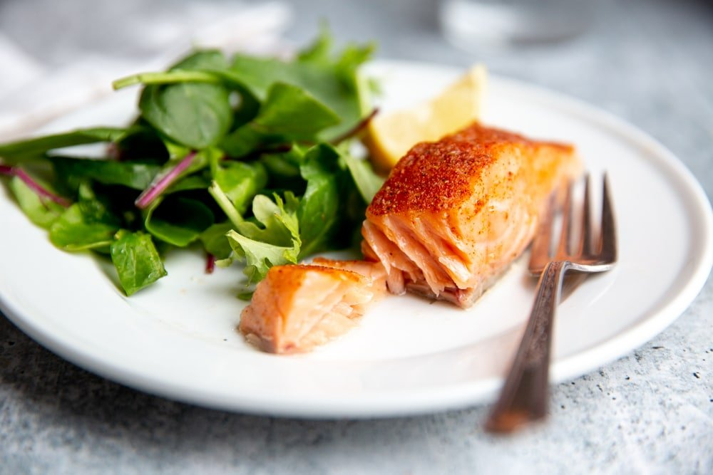 A slow cooker salmon fillet on a plate with a fork, with salad greens alongside.