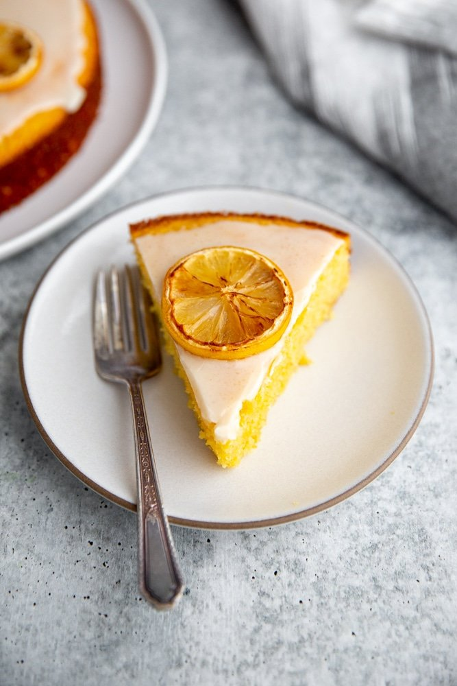 A slice of glazed lemon olive oil cake on a plate, topped with a caramelized lemon slice.