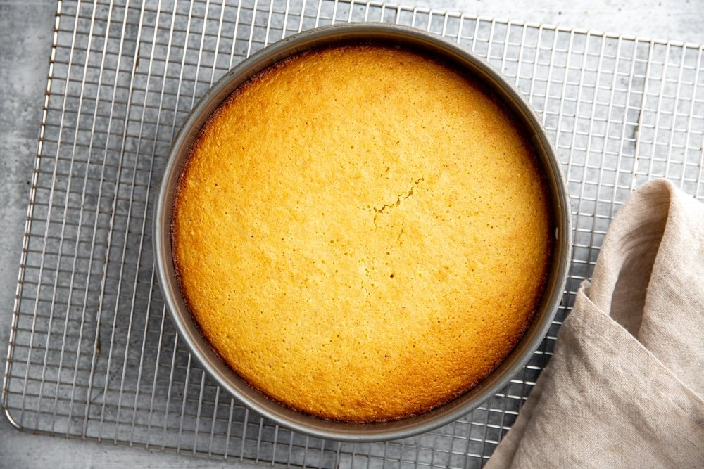 The baked lemon olive oil polenta cake on a cooling rack.