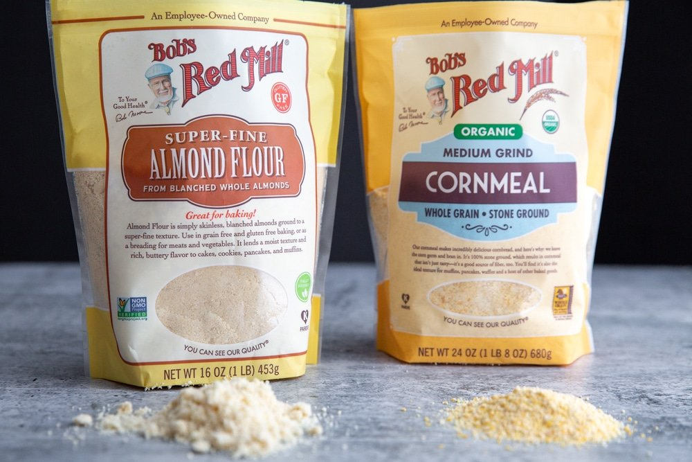 A bag of Bob's Red Mill Super-Fine Almond Flour and a bag of Bob's Red Mill Medium Grind Cornmeal on a counter.
