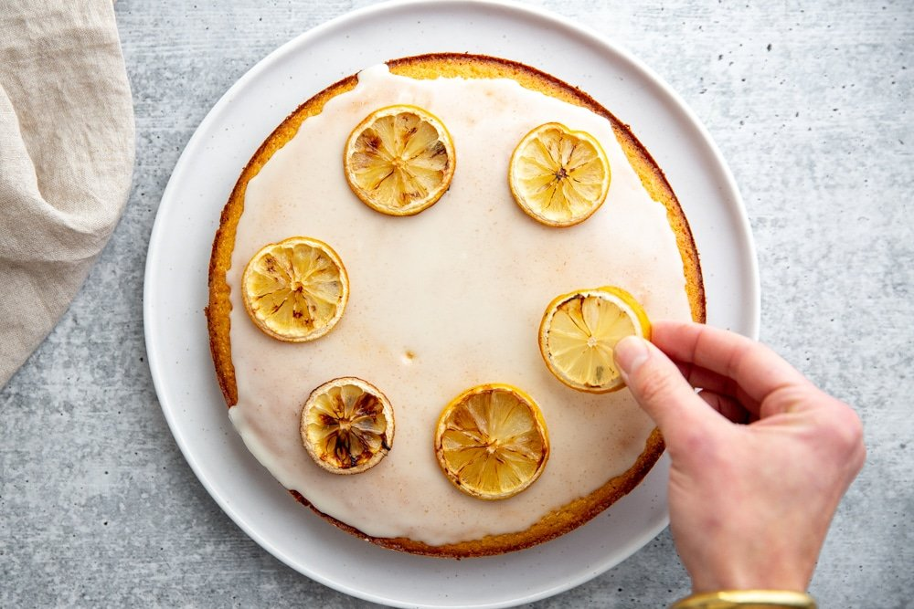 Hand placing a baked lemon slice on top of the cake.