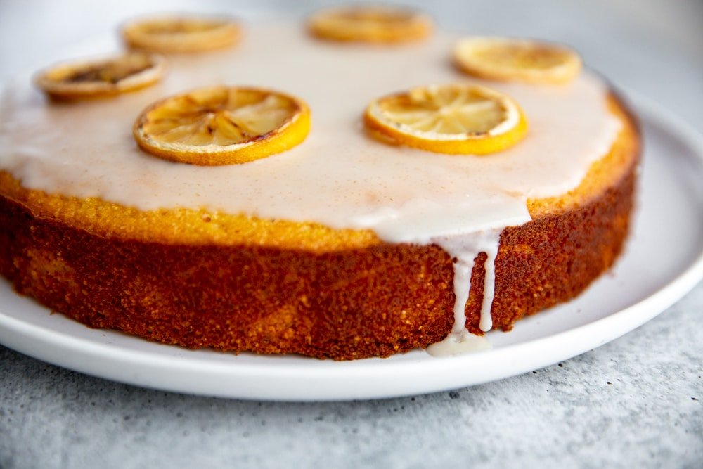 Gluten free lemon olive oil cake on a platter, garnished with baked lemon slices.